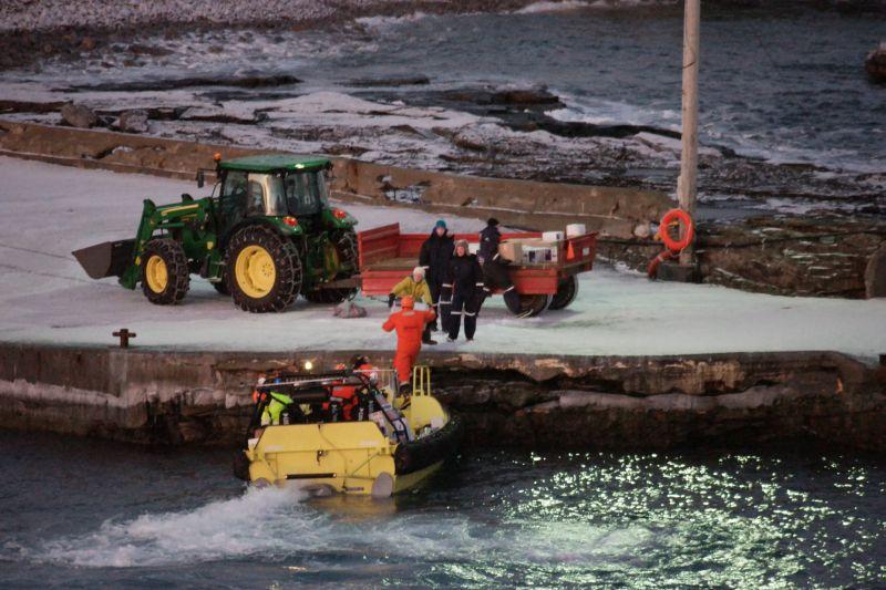 Sjøbjørnen fra KV Svalbard ligger inne ved kaia og det lempes esker med nye forsyninger, utstyr og post. Foto: BOF.