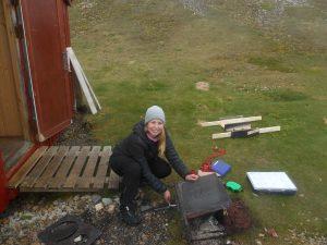 Kristine N.T. demonterer den gamle ovnen før transport